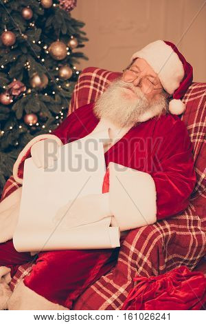 Portrait Of Tired Santa Claus Sleeping And Holding Paper Roll Of Wishlist