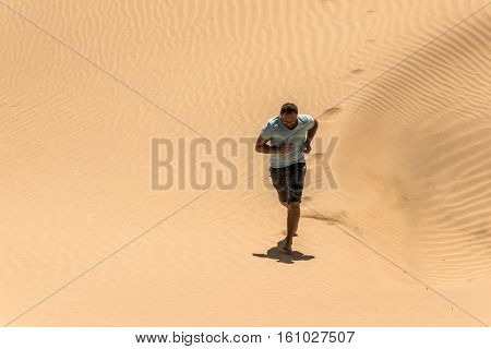 Man tourist in desert rub al khali in Oman running in sand 3