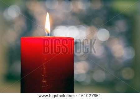 Candles light. Christmas candle burning at night. Abstract candle background. Golden light of candle flame. Closeup of a red candle with creamy bokeh background.