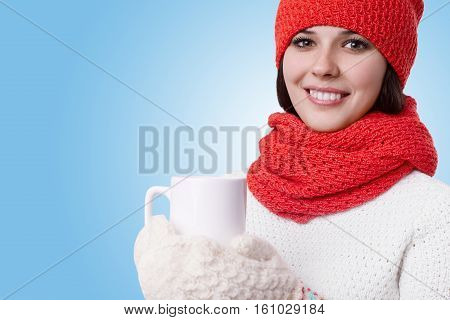Beautiful young woman with charming smile and bright eyes wearing warm knitted winter clothes enjoying winter holidays with cup of hot tea. Winter happiness holidays people hot drinks concept.