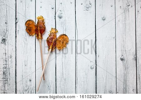 Set Of Decorative Sweet Shugar Bonbons Sugar Cock On Wooden White Background