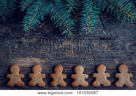 Christmas fir tree with gingerbread men cookies on old wooden background with space for text. Merry Christmas and Happy New Year. Xmas concept. Top view. Copy space.