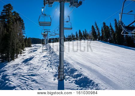 Riding up ski lift on a nice blue bird day at Red River , New Mexico , USA in the Sangre De Cristo Mountains on a sunny winter ski day