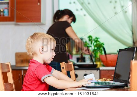 Technology and early education. Spending time with family eat together. Child use laptop for fun and learning. Boy sit with computer mother cooking dinner in kitchen.