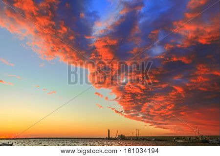 Molfetta's harbour dominated by orange clouds at sunset: in the background the lighthouse and breakwater.Apulia,Italy.