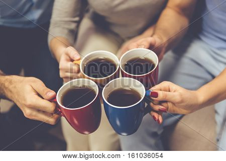 Cropped image of young people drinking tea while spending time together at home
