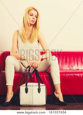 Elegant outfit. Female fashion. Blonde woman wearing fashionable clothes high heels with bag handbag sitting on red couch. Toned image