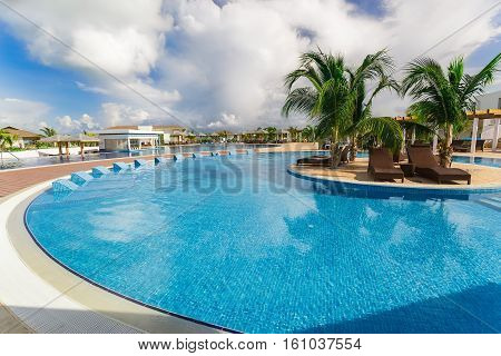 Cayo Guillermo island, Iberostar Playa Pilar hotel, Cuba, June 28, 2016, nice beautiful inviting view of a curved comfortable swimming pool with ceramic beds on blue sky background