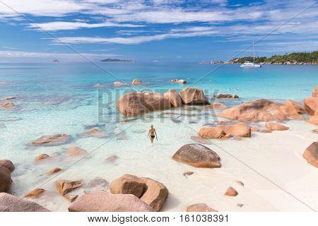 Woman wearing stylish bikini enjoying swimming and snorkeling at amazing Anse Lazio beach on Praslin Island, Seychelles. Summer vacations on picture perfect tropical beach concept.