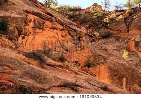 ZION NATIONAL PARK, UT - MARCH 30: Hikers stop for photographs along the popular Hidden Canyon Trail March 30, 2016 in Zion National Park, UT.