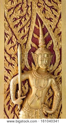 seraph wood carved gold paint on temple door Thailand.