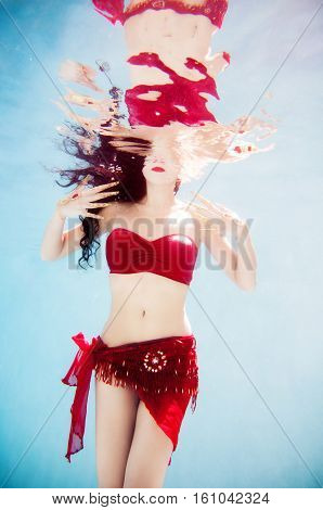 An artistic underwater portrait of a female model wearing a red bandeau top gold Thai fingernails and a jewel headpiece.