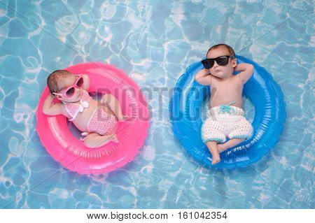 Two month old twin baby sister and brother sleeping on tiny inflatable pink and blue swim rings. They are wearing crocheted swimsuits and sunglasses.