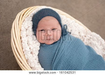 An alert three week old newborn baby boy swaddled in a blue wrap and wearing a blue bonnet. He is lying in a wicker basket and looking at the camera. Shot outdoors on a sandy beach.