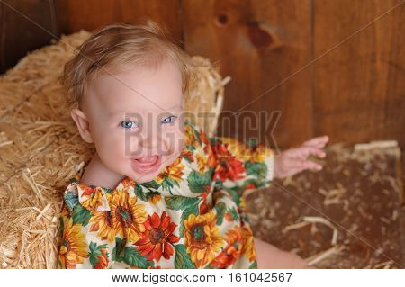 A laughing six month old baby girl wearing a floral romper in fall colors. She is sitting and leaning against a small straw bale. Shot in the studio on a wood paneled floor and background.