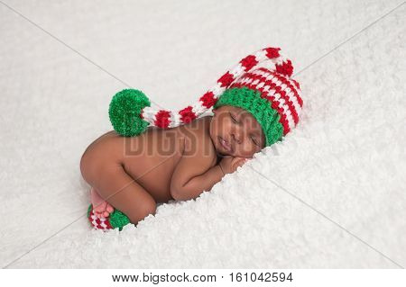 A one month old baby girl wearing a crocheted red white and green stocking cap with matching leg warmers. Photographed on a white fluffy blanket.