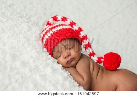 A one month old baby wearing a white and red crocheted stocking cap. Photographed on a white fluffy blanket.
