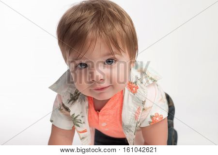 A curious ten month old baby boy looking into the camera. He is crawling on a white seamless background.