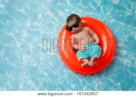 Eleven day old newborn baby boy sleeping on a tiny orange inflatable swim ring. He is wearing turquoise blue crocheted board shorts and black sunglasses.