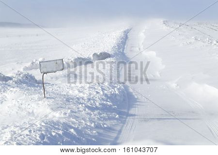 A rural mailbox by a country road which is closing with blowing drifting snow in Pennsylvania USA.