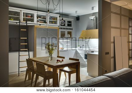 Amazing kitchen in a modern style with gray walls, white lockers and shelves with accessories. There is a wooden table with chairs, dark ladder, fridge, sink, oven, stove, glowing kitchen hood, sofa.