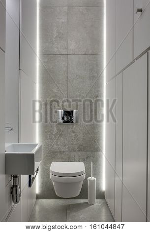 Restroom in a modern style with gray tiles and white lockers. There is a white toilet and a toilet brush, white sink with a faucet, chrome wall flush button. Backlight shines from behind. Vertical.