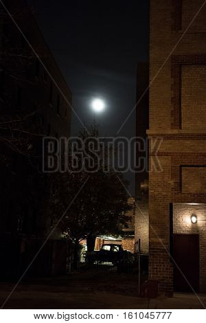 Dark urban downtown city alley at night with moon and car.