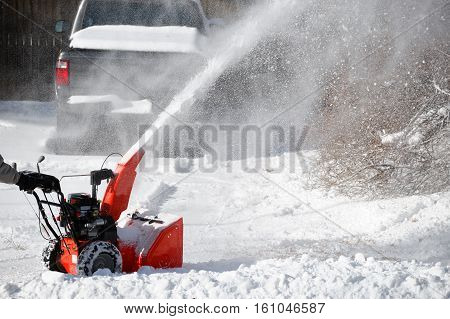 snow blower blowing snow away from driveway