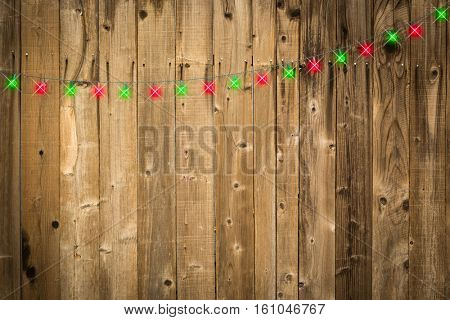 Lustrous Wooden Background with Bright Green and Red Christmas Lights.