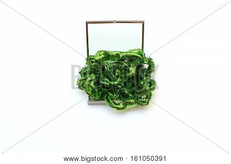 Glass box with silver details filled green tinsel. Festive decorations on a white background. Top view, flat lay, copy space.