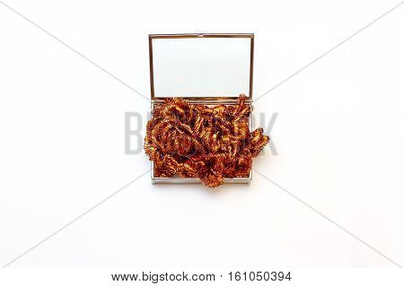 Glass box with silver details filled orange tinsel. Festive decorations on a white background. Top view, flat lay, copy space.
