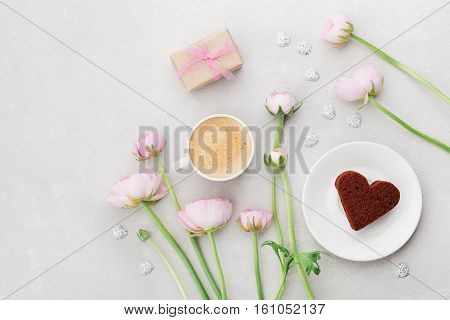 Breakfast for Valentines or Mothers day with cup of coffee, gift flowers and cake in shape of heart on gray table from above in flatlay style.