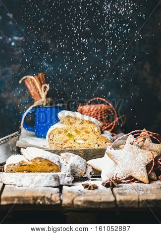 Piece of Traditional German Christmas cake Stollen with festive gingerbread star shaped cookies and falling sugar powder, selective focus, dark blue grunge background, copy space, vertical composition