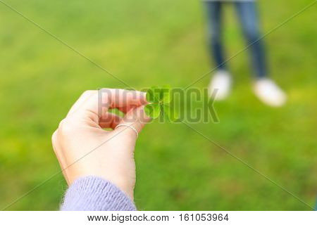 Female hand holding a four-leaf clover - shot