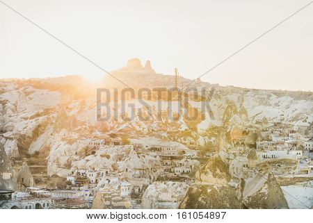 Sunset over Goreme village, cave houses and Uchisar castle in Cappadocia region, Central Turkey. Traditional landscape of Cappadocia