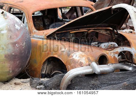 Vintage destroyed classic cars taken in a countryside junkyard