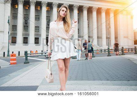 Fashionable city girl concept. Gorgeous young woman walking near city building wearing summer outfit clothes.