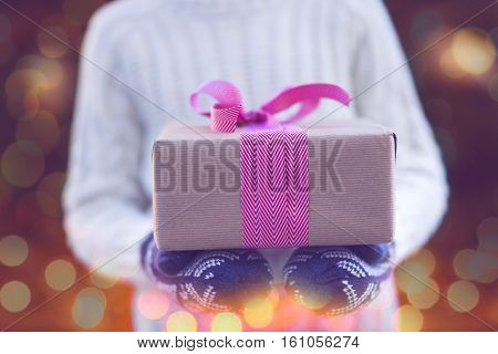 close-up of nicely wrapped christmas gift being held by the kid in mittens by christmas tree with lights toned image