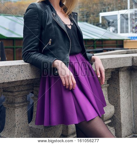 Female scater skirt and leather jacket. Girl wearing sexy fashionable outfit with black leather jacket and purple circle skirt. Model girl in fashion skirt.