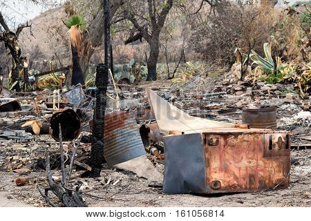 Destroyed home with charcoaled objects and trees caused from a fire
