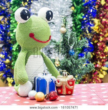A cute little green frog sitting Christmas party with gifts.