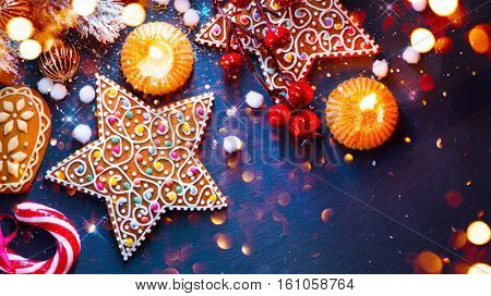 Christmas Holiday Background with ornate Gingerbread cookies, Candy Cane and evergreens border over black background table. New year food. Xmas decoration.