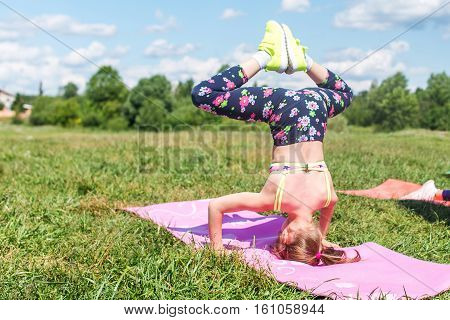Rear view fit girl doing headstand in park.