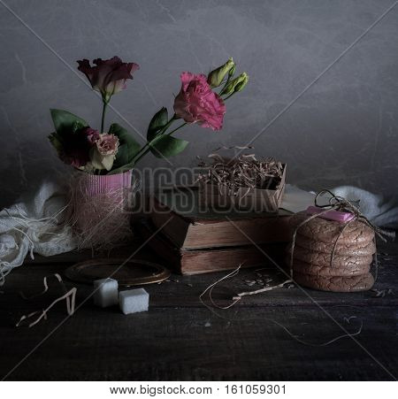 vintage. old books, rose, cakes drapery on wooden table