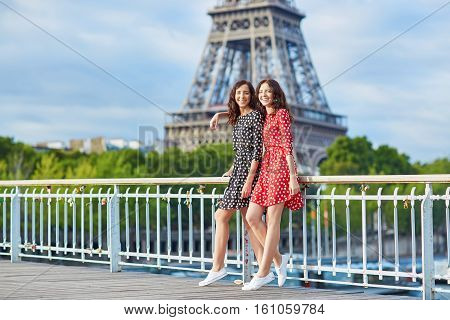 Twin Sisters In Front Of The Eiffel Tower In Paris, France