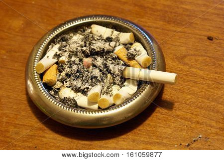 This ash tray is being used and has been filled.