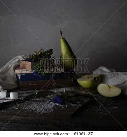 vintage. old books, bouquet of flowers, drapery on a wooden table. dark backgrounds