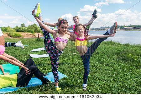 Kids gymnasts warming up in pair outdoors