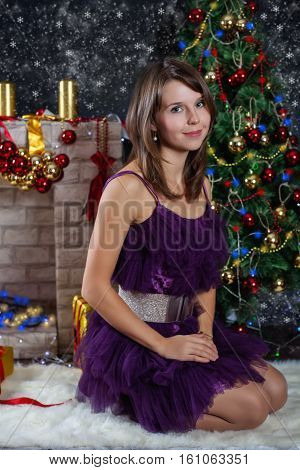 Young woman posing in front of the Christmas Scene. Posing smiling