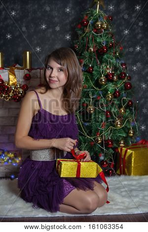 Young womanl unleashes the gift. Christmas Scenes. Posing smiling